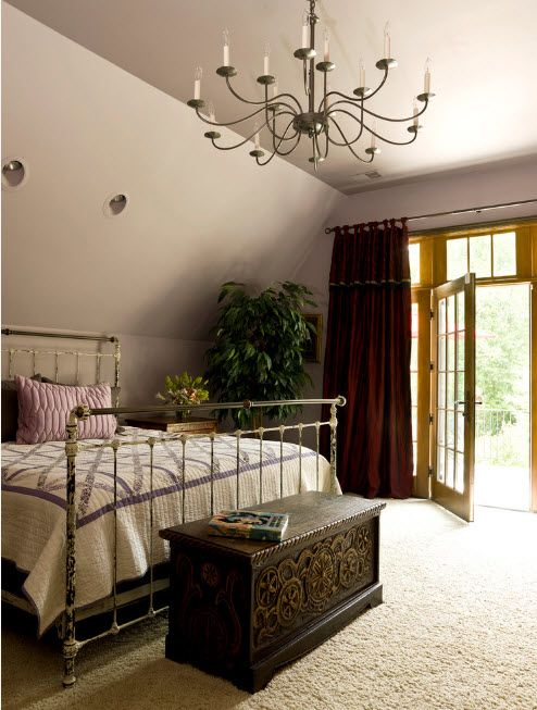 Spacious room with the entrance to the backyard and slanted ceiling with large metal framed bed