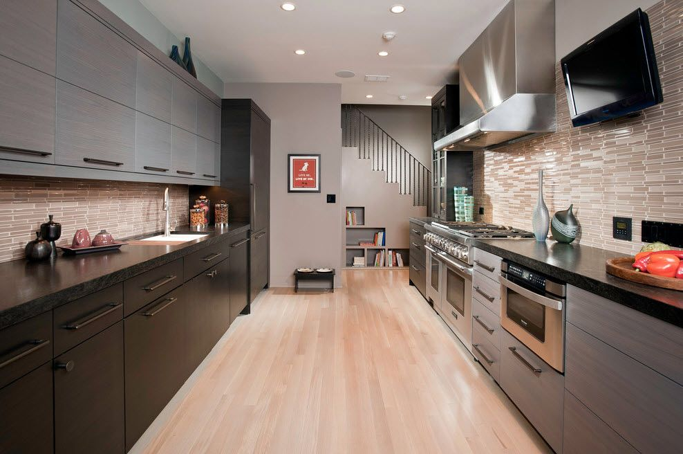 Glancing bleached oak colored laminate in hi-tech styled kitchen with steel shining appliances