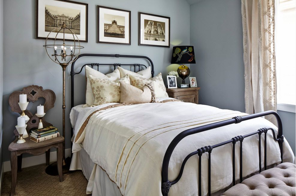 Wrought-iron Bed as a Stylish and Functional Interior Element. typical Classic ambience with blue painted walls