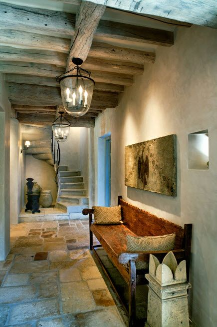 Spiral staircase and open wooden ceiling beams for the Mediterranean styled house's hall