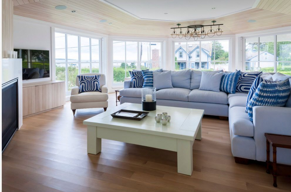 Jetty formed living room with bay window and satin olive colored coffee table