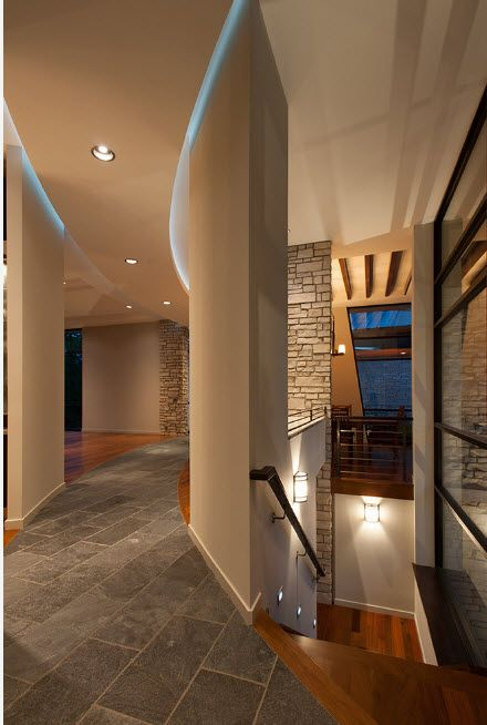 Hi-tech design with artificial stone slabs trimmed accent wall near the stairs in the two-storey house