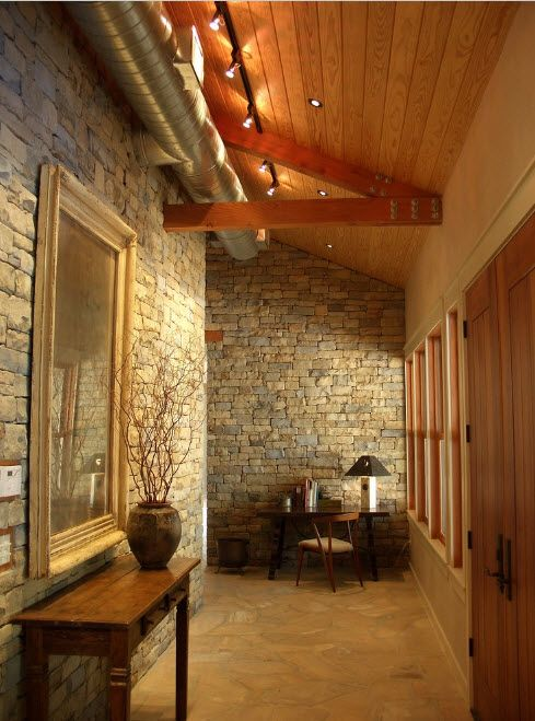 Long hall in the classic styled house with stone finished walls