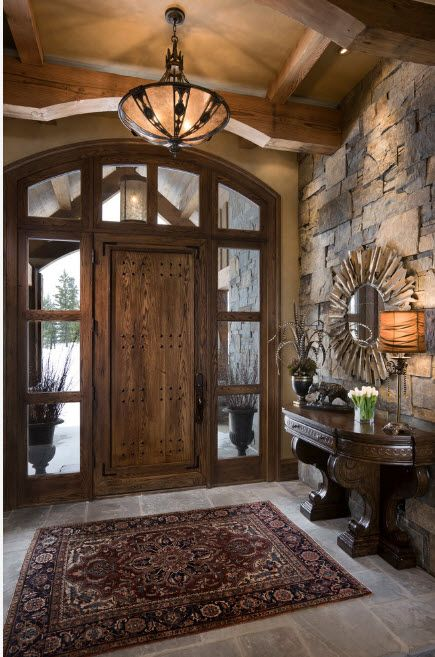 The Use of Decorative Stone for Modern Interiors' Finishing. Entrance door with glass frame and Modern granite trimming