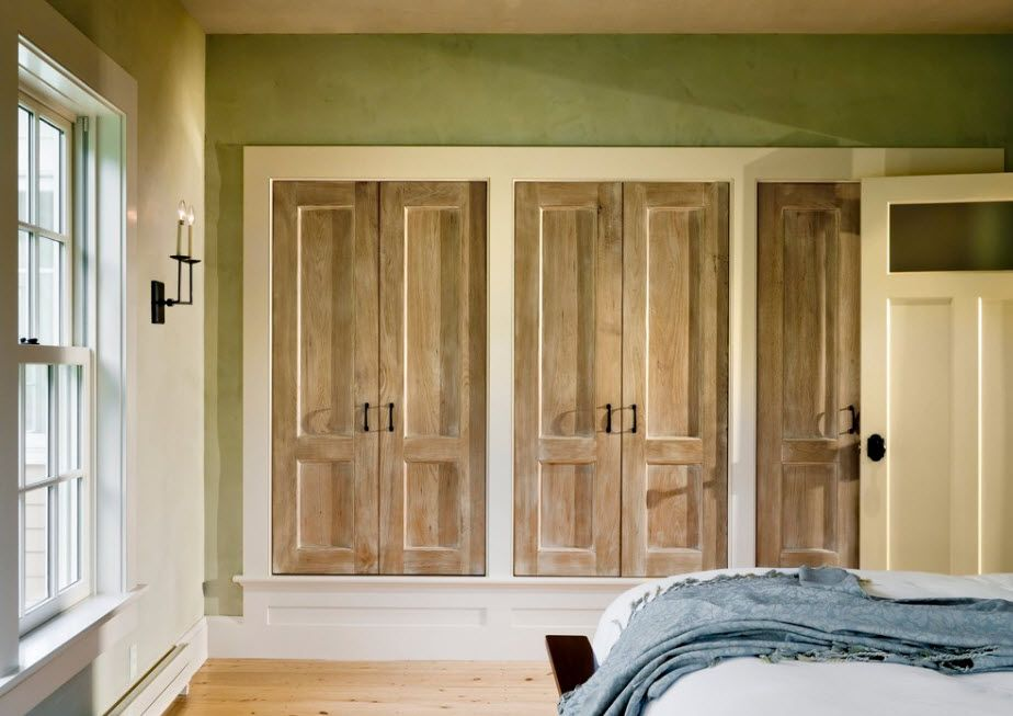 Doors to cabinets as if fake window shutters in the classic decorated bedroom with olive wall paint