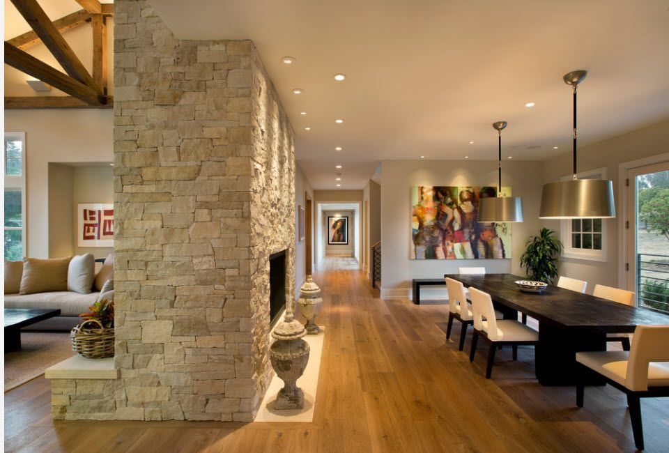 The Use of Decorative Stone for Modern Interiors' Finishing.  Classic living room with fireplace and dining zone, also and accent wall in light stone