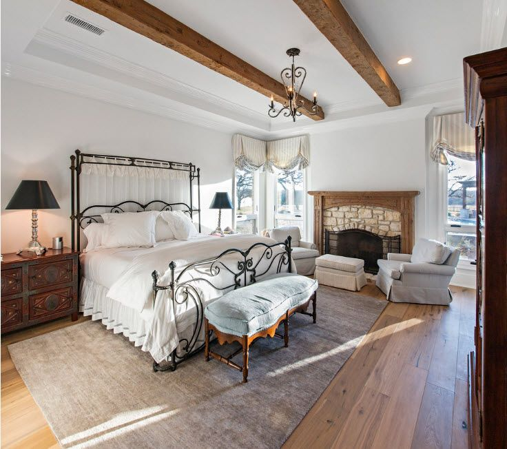 Wrought-iron Bed as a Stylish and Functional Interior Element. Open ceiling beams in white room with open layout