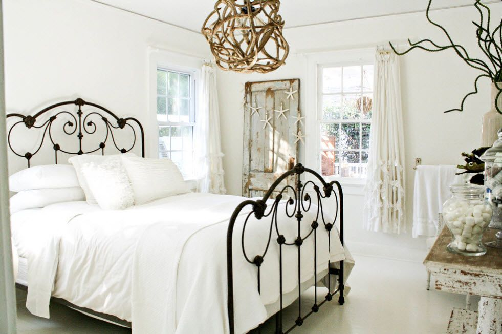 Wrought-iron Bed as a Stylish and Functional Interior Element. Spectacular black frame of the bed with golden clew of the lamp shade above