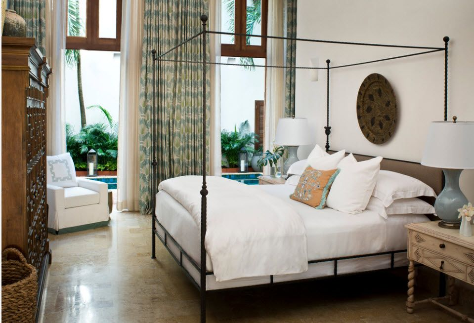 Wrought-iron Bed as a Stylish and Functional Interior Element. Private house among the natural greenery with the royal bed with canopy frame