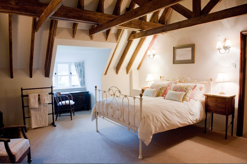 Wrought-iron Bed as a Stylish and Functional Interior Element. Spectacular open ceiling construction of wood in pronounced loft room