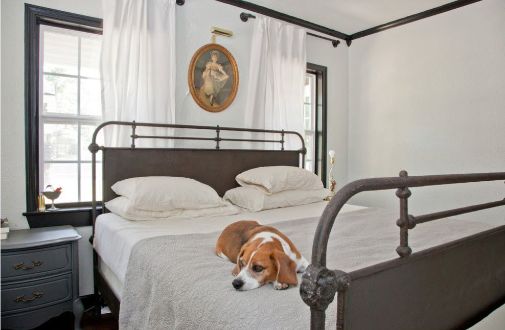 Wrought-iron Bed as a Stylish and Functional Interior Element. Simple and cute Classic ambience with white tulle curtains