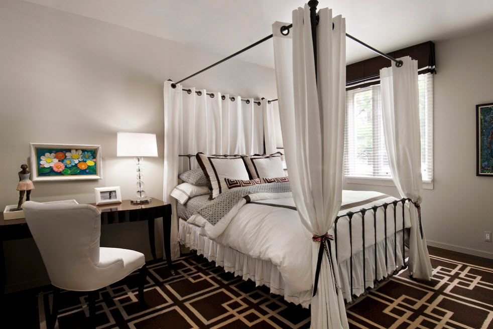 Wrought-iron Bed as a Stylish and Functional Interior Element. High canopy with grommet curtains in the large space in white and dark contrast
