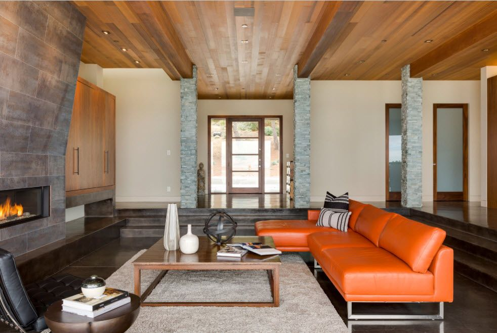 Wooden ceiling and granite finished accent wall with artificial fireplace at the Modern styled living room with orange leather angular sofa