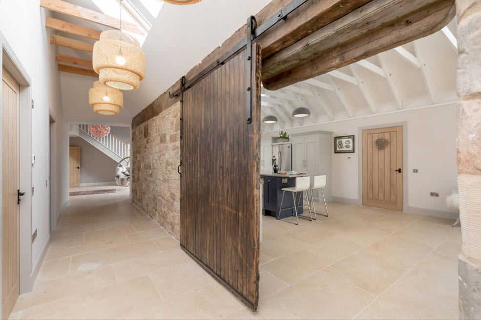 Raw treated wooden sliding doors for the pure Rustic style of the interior with stone wall finishing