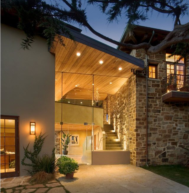 Unique hi-tech design of the house's facade with total glass panoramic entrance and stone trimmed walls