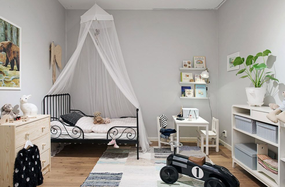 Spacious children's room bed with transparent tulle as the canopy