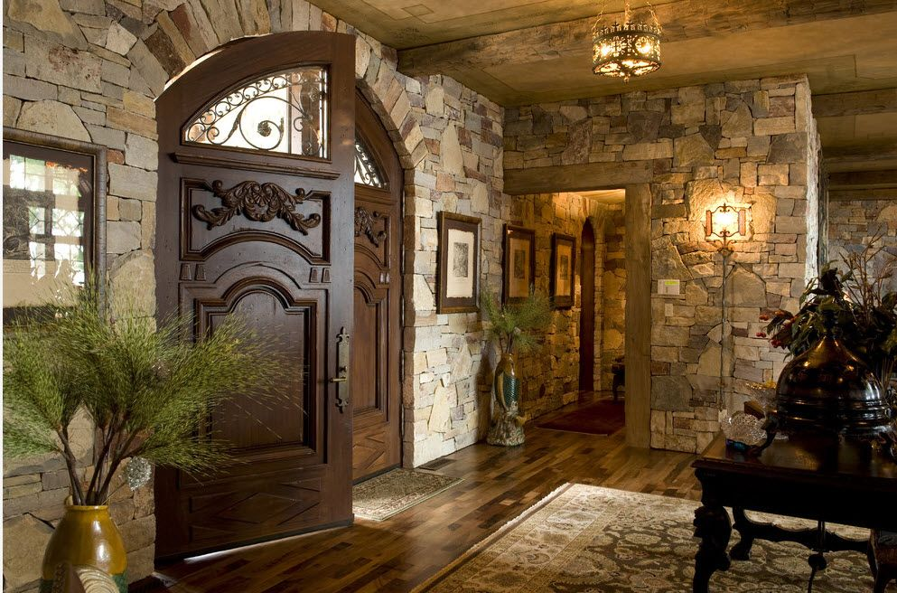 The Use of Decorative Stone for Modern Interiors' Finishing. Greek styled ateroom with heavy  carved door