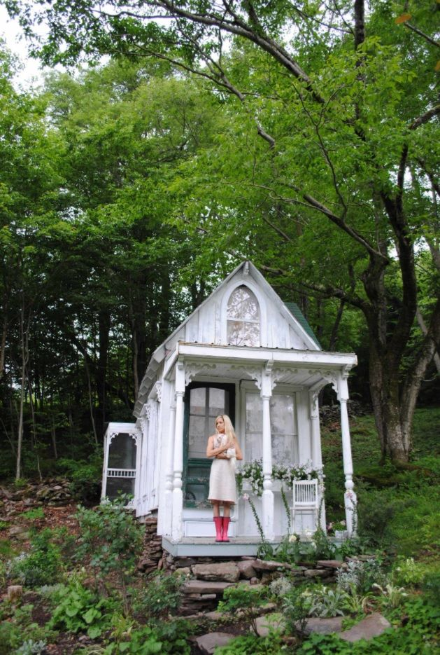 Modern Designs for Tiny Homes. White wooden house among the primeval nature