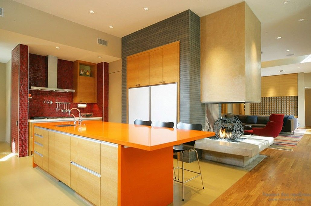 Unexpected orange glossy kitchen island in the spacious Modern and hi-tech styled room