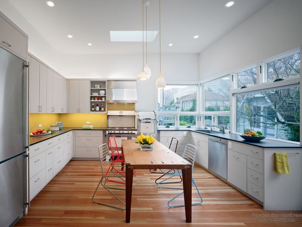 Yellow glossy LED-enlighted splashback in the modern styled kitchen
