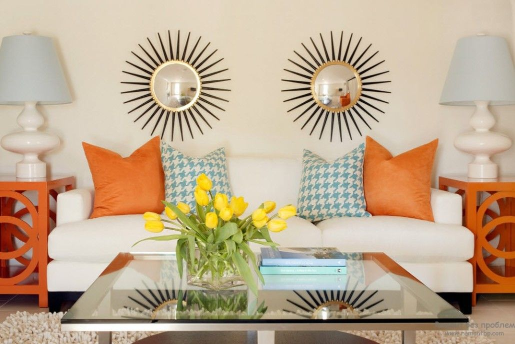 Sunburst mirrors above the sofa decorated with the colorful pillows