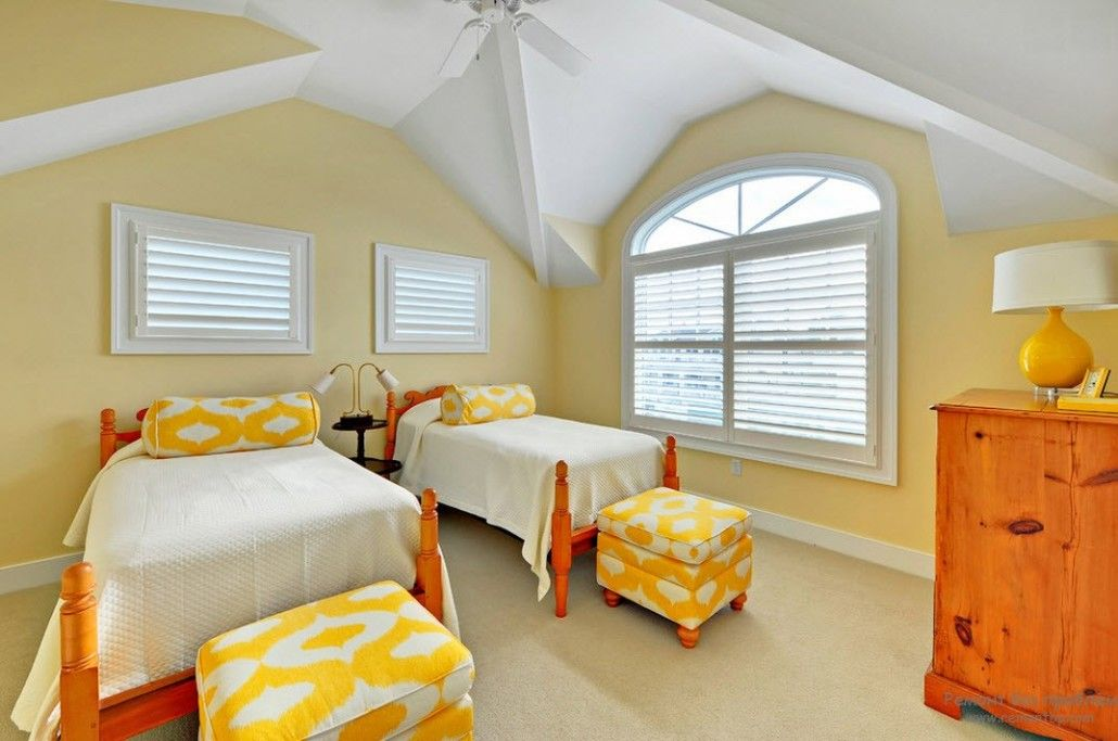 Loft architecture of the yellow painted bedroom and two plain beds