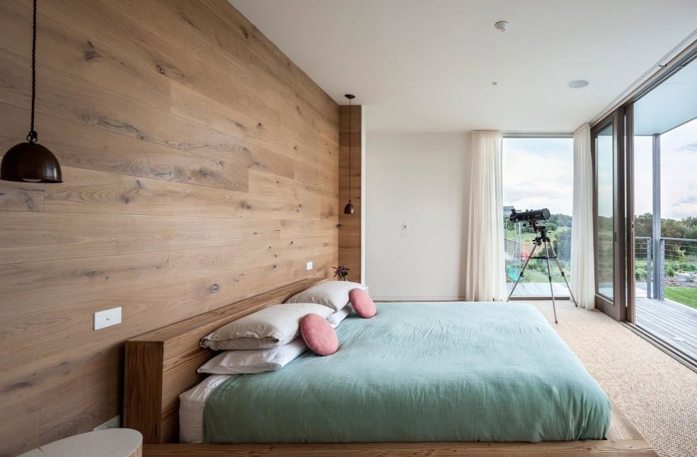 Wooden sheathed headboard wall in the large fresh white bedroom