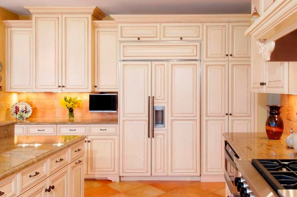 Total classic style for light designed kitchen with built-in refregerator hidden upon the classic facade