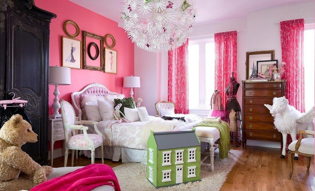 Kids' room with accent pink wall decorated with picture frames