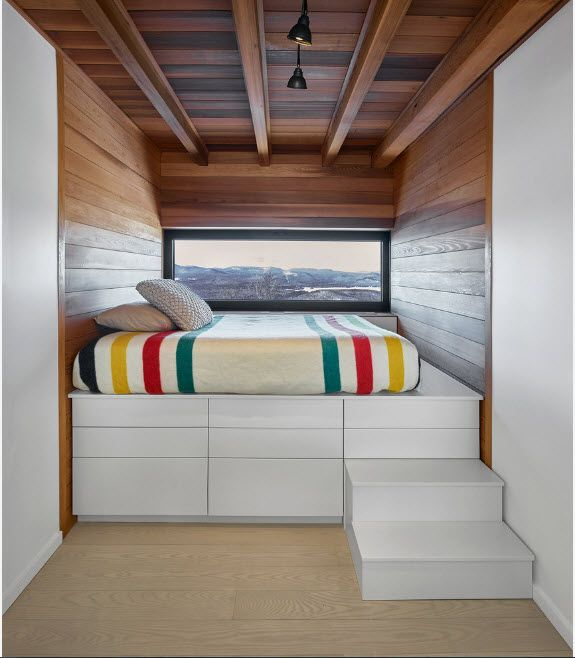 Unusual loft styled recess with open ceiling beams and wooden sheathing of the walls and podium bed