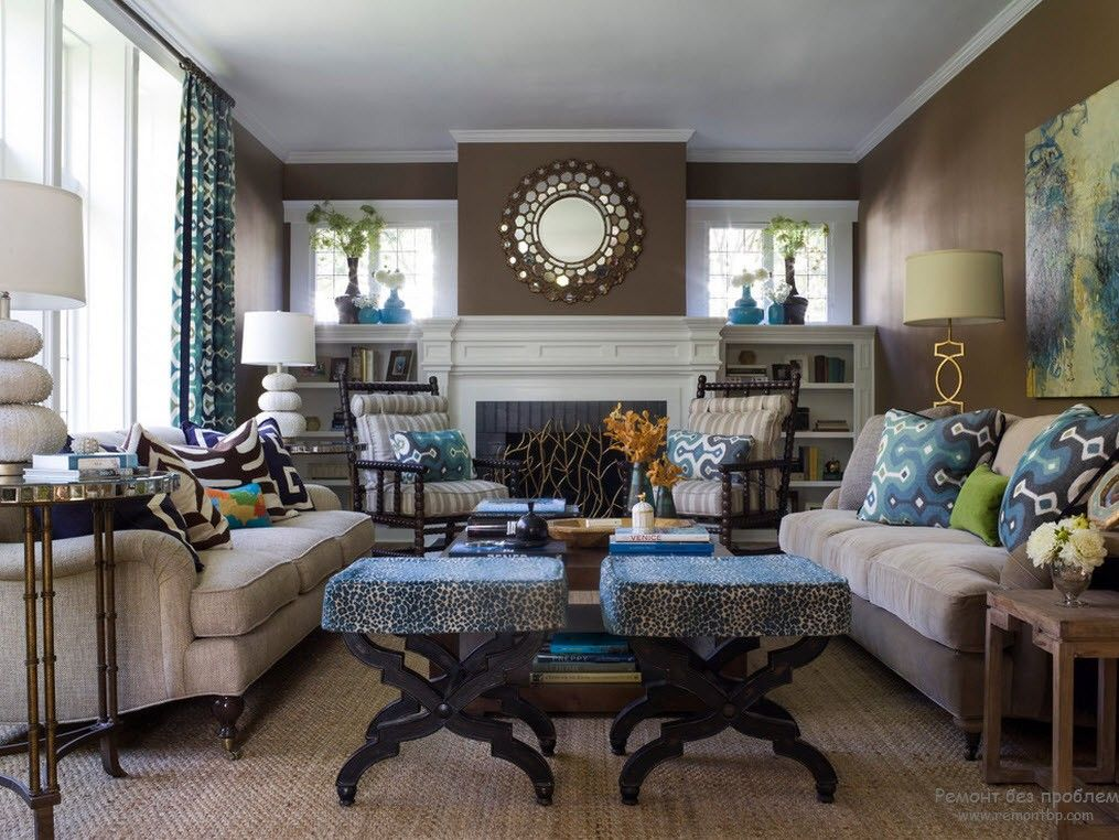 Classic large living room setting with fireplace, chocolate brown wall paint and creamy upholstered sofas
