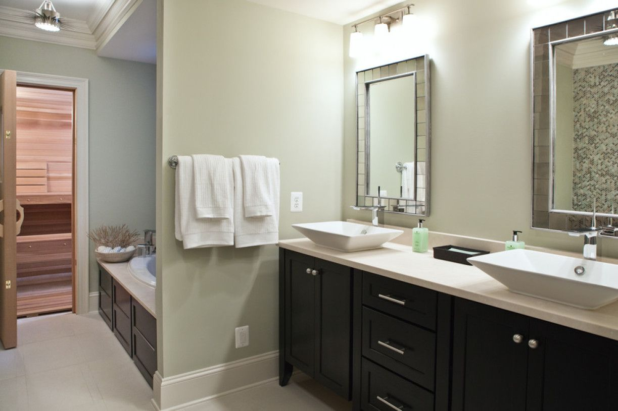 Bathroom with dark wooden vanity and pale olive painted walls