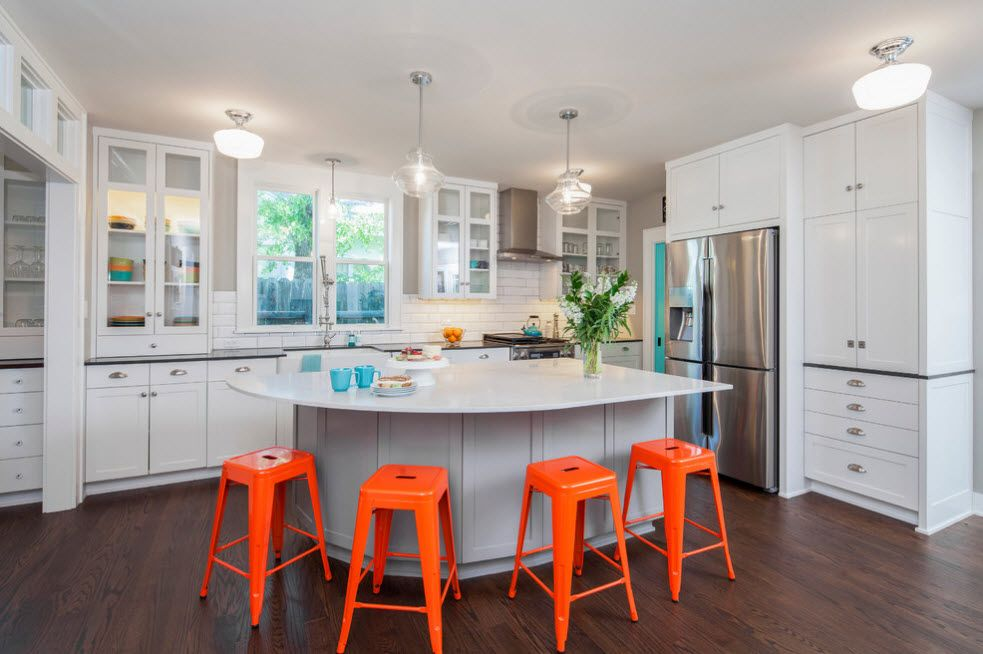 Refrigerator in Modern Kitchen Interior Design. Contrasting orange bar stools in the strict Scandinavian gray and white interior