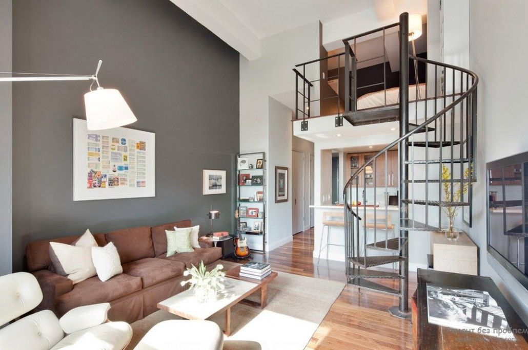 Loft design for modern two-stirey apartment with spiral staircase and solid gray wall as a background for leisure corner