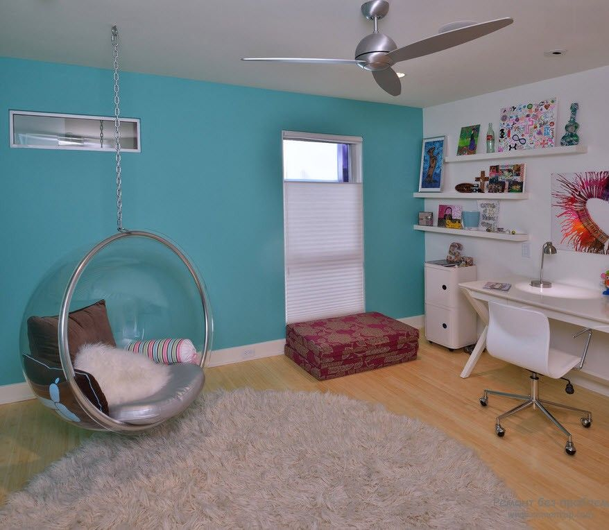 Turquoise accent wall in the boxed minimalistic room with hanging plexiglass chair and silver fan