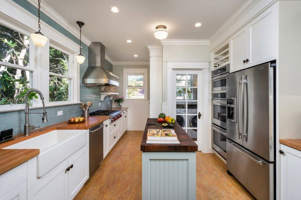 Refrigerator in Modern Kitchen Interior Design. Functional space with funriture set and an island in the center with hob and fridge at different sides