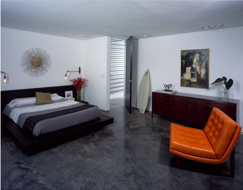 Casual styled bedroom in light colors with bright orange armchair