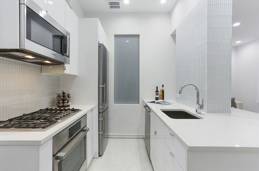 Matted white kitchen design with glancing steel surfaces of the hob and fridge look fascinating