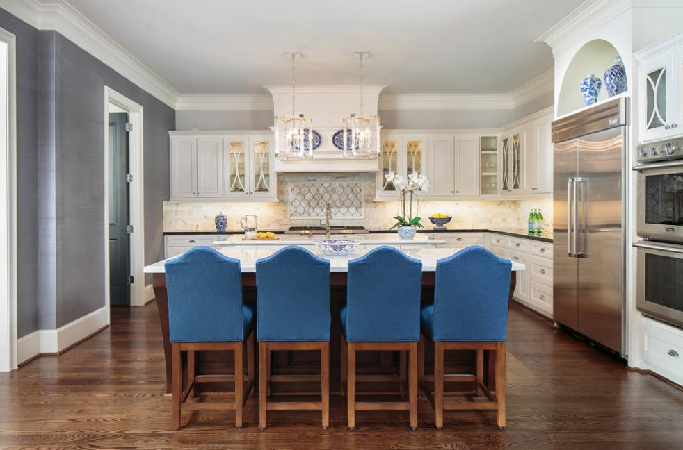 Refrigerator in Modern Kitchen Interior Design. Classic atmosphere in the cooking zone with blue backs of wooden chairs