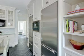 Refrigerator in Modern Kitchen Interior Design. White Classic furnture facades with stucco imitation and steel surface of the fridge