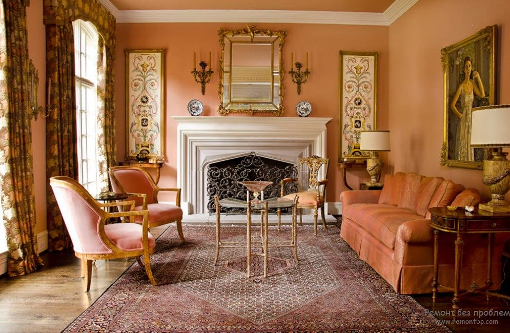 Classic style in the warm peachy living room with the fireplace and golden frames of paints