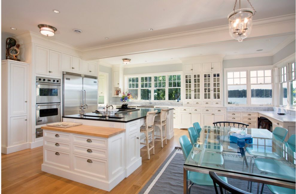 Refrigerator in Modern Kitchen Interior Design. Large private house's cooking space with island and furniture in white