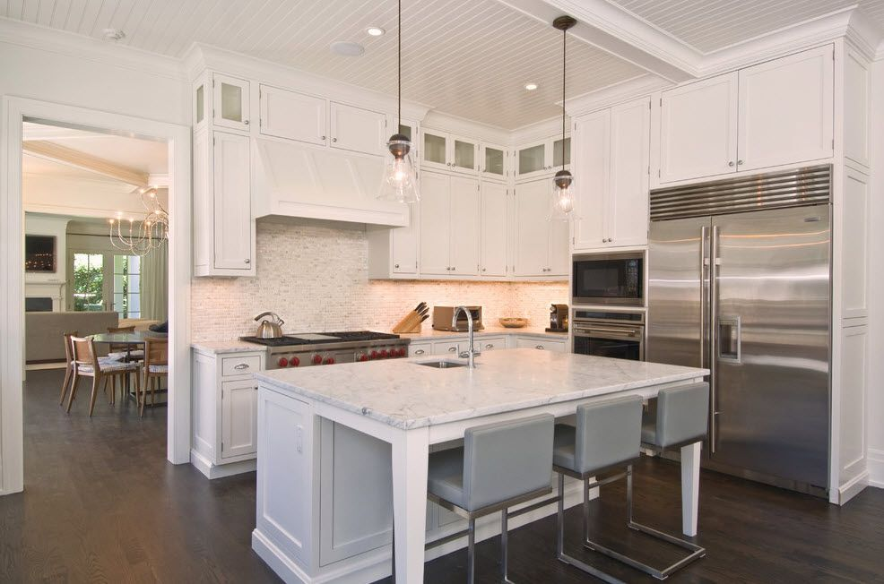 Refrigerator in Modern Kitchen Interior Design. Hi-tech style with steel surfaces of appliances and plastic countertop of the island