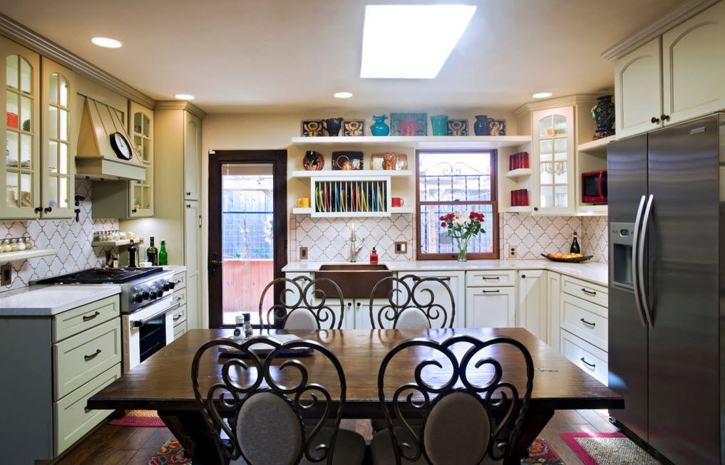 Carved black chairs and the white kitchen interior in aesthetical contrast