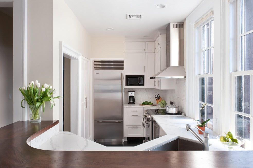 Refrigerator in Modern Kitchen Interior Design. Unusual shape of kitchen zone in the studio apartment
