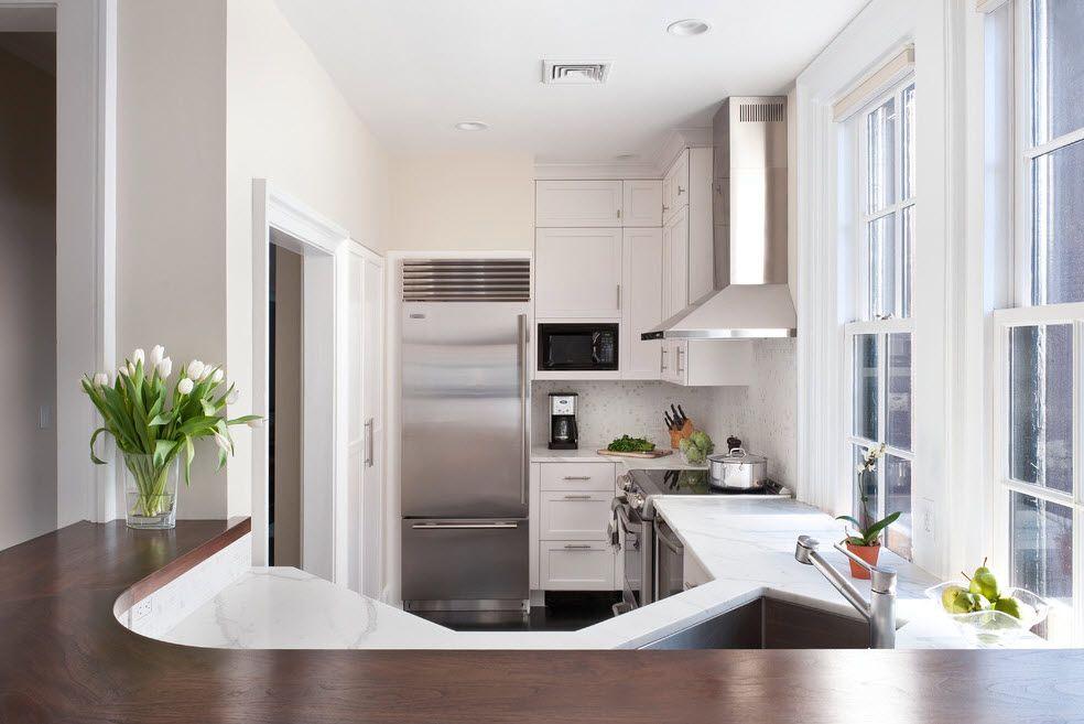 Refrigerator in Modern Kitchen Interior Design. Unusual shape of kitchen zone in the studio apartment