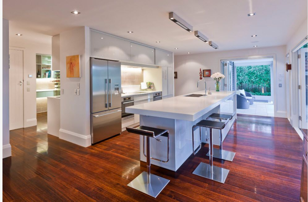 Dark wooden laminate at the Modern styled kitchen with steel surfaces of appliances and bar stools