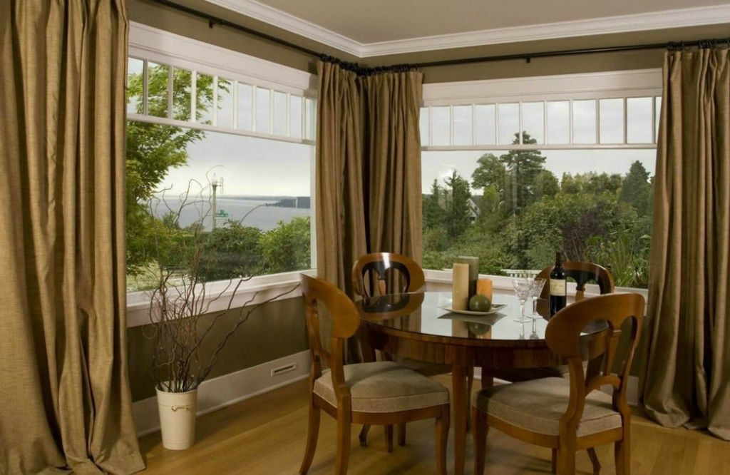 Panoramic windows in the suburb house's interior and olive curtains