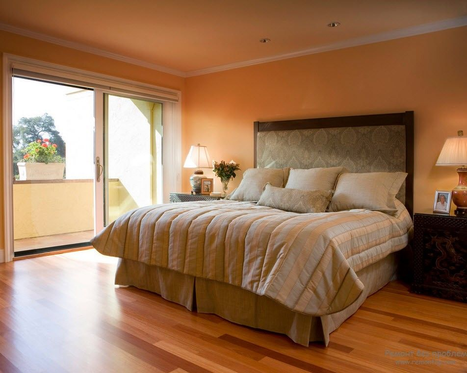 Peach painted walls and natural wooden floor for minimalstic bedroom