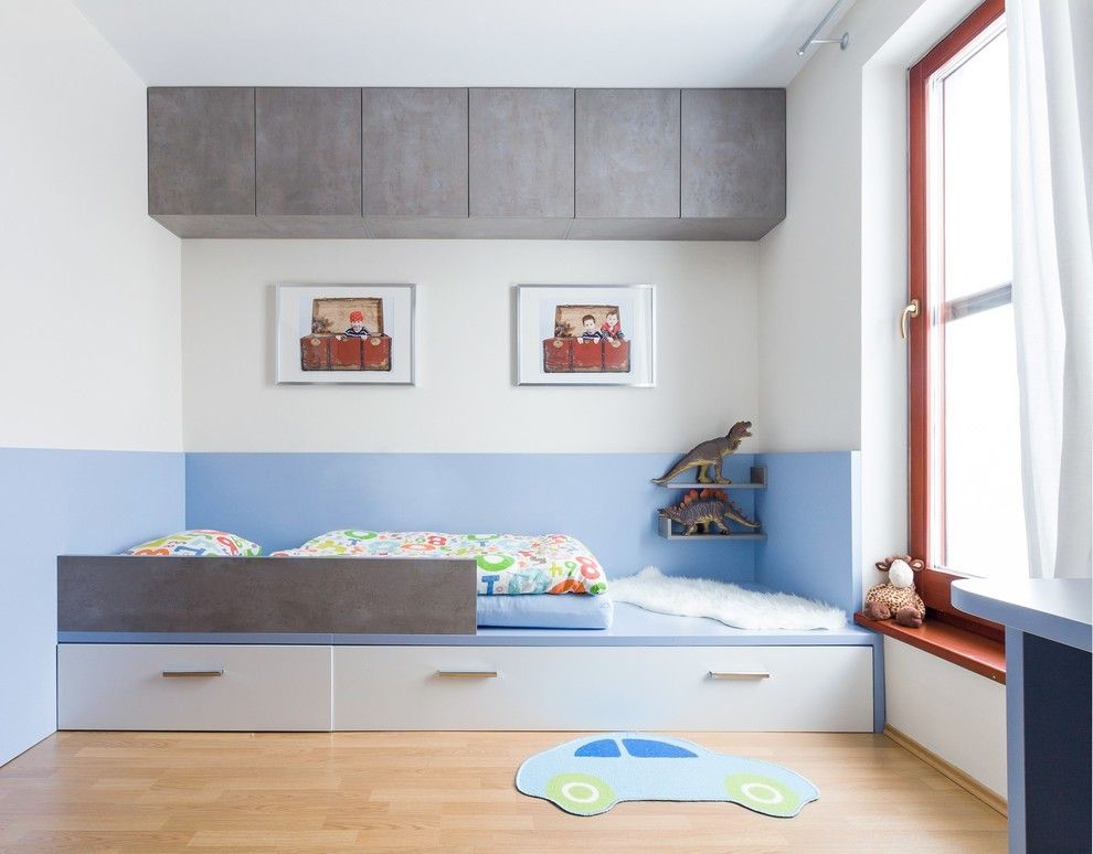 Blue and white wall painted kids' room with gray inlays of storage